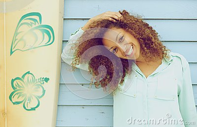 Pretty young lady smiling and leaning on surfboard