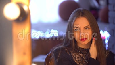 Pretty, young and sensual woman with beautiful make-up and long hair in the evening black dress looking at her. Pretty, young and sensual woman with beautiful stock footage