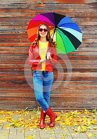 Free Pretty Young Smiling Woman With Colorful Umbrella Wearing A Red Leather Jacket And Rubber Boots In Autumn Over Wooden Background Royalty Free Stock Photos - 78645428