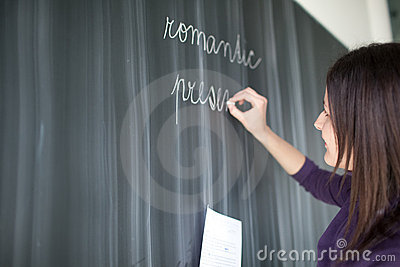 Pretty young  student writing on the blackboard