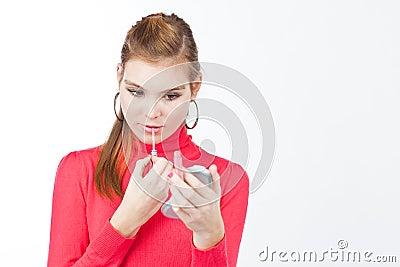 Pretty young woman applying lip gloss