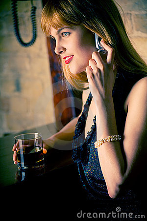 Pretty young woman at bar counter, on mobile phone
