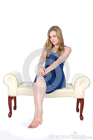 Pretty young woman in blue dress and bare feet