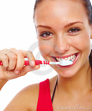 Stock Photography: Pretty young woman brushing her teeth ...
