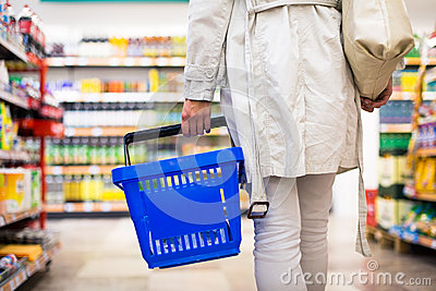 Pretty young woman buying groceries in a supermarket
