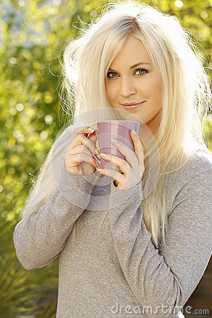 Pretty young woman with a cup of coffee outside