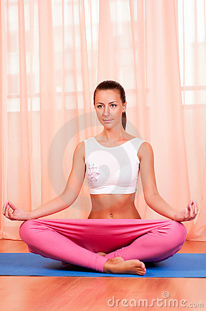 Pretty young woman doing yoga exercise on mat