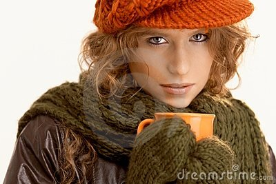 Pretty young woman dressed up warm drinking tea