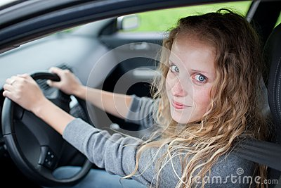Pretty young woman driving her  car