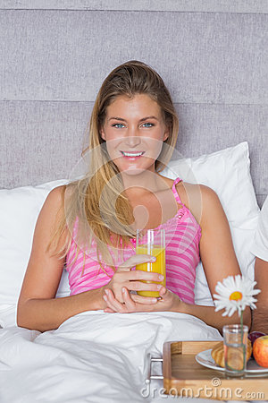 Pretty young woman having breakfast in bed with partner