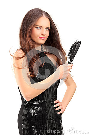 Pretty young woman holding a hair brush