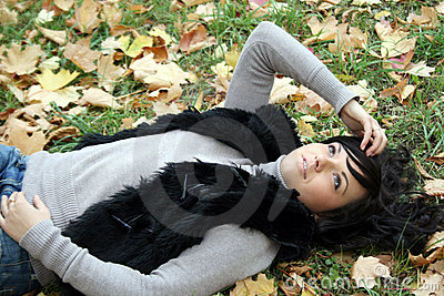 Pretty young woman lying in autumn park