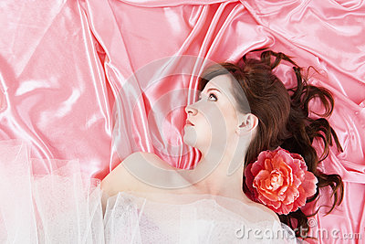 Pretty young woman lying on pink background