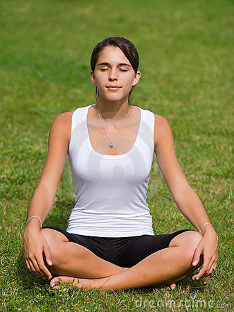Pretty young woman meditating on grass