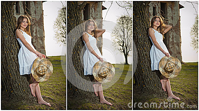 Pretty young woman posing in front of the farm. Very attractive blonde girl with white short dress holding a hat. Romantic girl