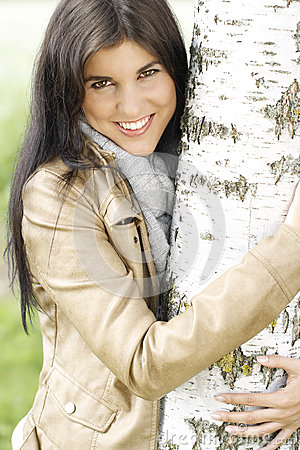 Pretty young woman puts her arms around a tree