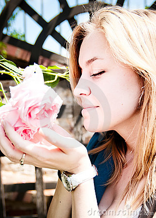 Pretty young woman smelling rose