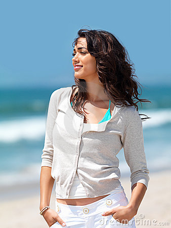 Pretty young woman standing on beach
