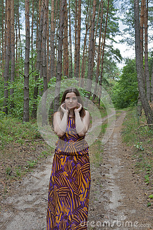 Pretty young woman standing on the forest road