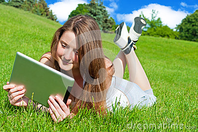 Pretty young woman with tablet lying on grass.