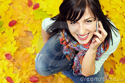 Pretty young woman talking on phone among leaves