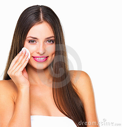 Pretty young woman using cotton on her face