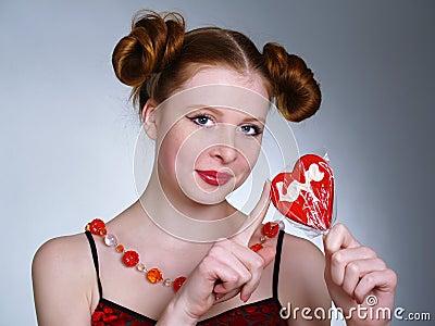 Pretty young women holding heart shaped lollipop