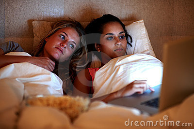 Pretty young women watching movie on laptop