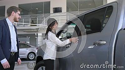 Prezent żona Atrakcyjnego faceta dziewczyny końcowi oczy i dawać samochód dla urodziny w przedstawicielstwo firmy samochodowej, zbiory