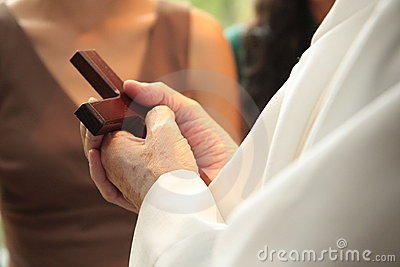 Priest holding cross in hands