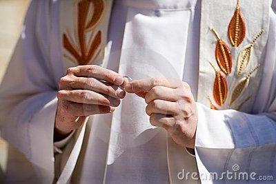 Priest holding wedding rings