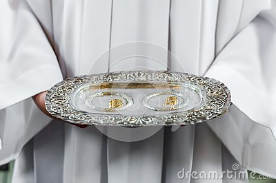 Priest and wedding rings on silver platter Stock Photo