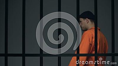 Prigioniero nervoso che cammina in cellula, giudizio aspettante, pensante alla fuga archivi video