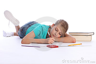 Primary school girl doing math homework on floor