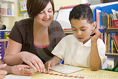 Primary school teacher helping boy learn numbers