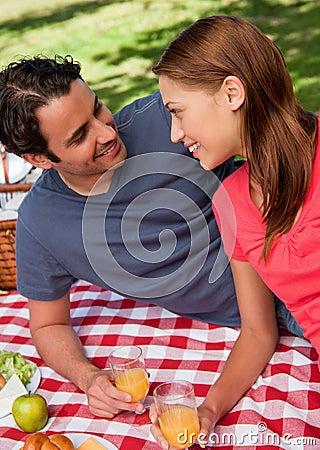 Primer de dos amigos sonrientes que mienten en una manta con una comida campestre