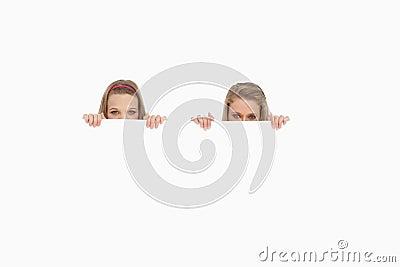 Primer de las mujeres jovenes que ocultan detrás de una muestra en blanco