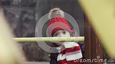 Primo piano di un'età 3-4 della ragazza in vestiti caldi che stanno meditatamente sul campo da giuoco variopinto luminoso, rallen video d archivio