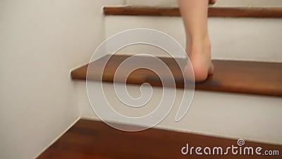 Primo piano I piedi nudi di una salita caucasica della donna alla cima delle scale di legno archivi video
