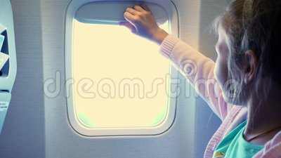 Primo piano Il bambino che la ragazza alza la tenda dell'oblò nella cabina dell'aeroplano, da là splende una luce intensa Ragazza archivi video