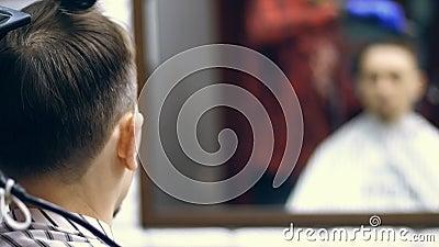 Primo piano, vista da dietro, in un negozio del baber, un salone di capelli degli uomini, taglio dei capelli di un uomo e disegna stock footage