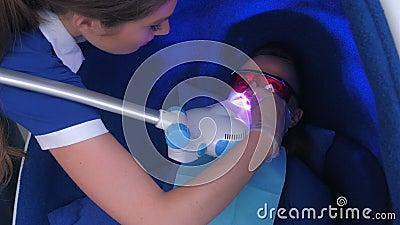 Procedimento cosmético de branqueamento LED para dentes femininos na estomatologia video estoque