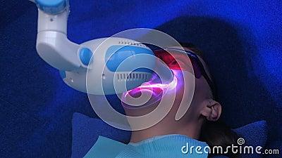 Procedimento cosmético de branqueamento LED para dentes femininos no estúdio de odontologia video estoque