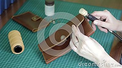 Procesamiento y fabricación de artículos de cuero con una herramienta de potencia en un fondo borroso de un taller almacen de video