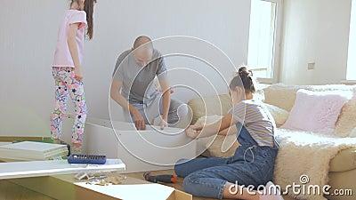 Proceso de montaje de muebles en un apartamento Dos adolescentes ayudan a su padre a montar un rack de madera almacen de video