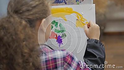 Processo di disegno: nello studio artistico dell'artista, ragazza con un dipinto a pennello su tela Mano dell'artista dei bambini stock footage