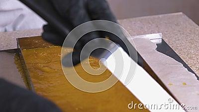 Producción de goma handmade Las manos en guantes cortaron la capa de goma con un cuchillo almacen de metraje de vídeo