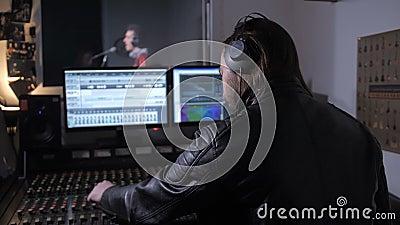 Productor musical de audífonos trabajando en la banda sonora almacen de metraje de vídeo
