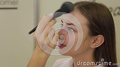 Profesjonalny twórca makijażu przylepia proszek do twarzy klienta pędzlem zbiory wideo
