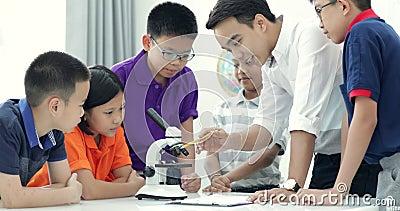 Professeur asiatique augmentant à l'étudiant dans le cours de Biologie avec le microscope clips vidéos